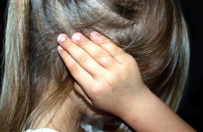bambina mano orecchio